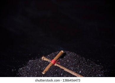 A wooden cross lies on the black ground. Prayer cross, amulet. Tied in the center with a red thread. Black background.