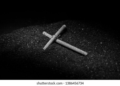 A wooden cross lies on the black ground. Prayer cross, amulet. Tied in the center with a red thread. Black and white photo.