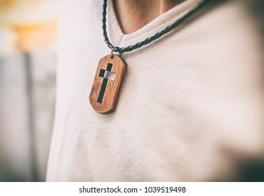 The wooden cross necklace on man's neck