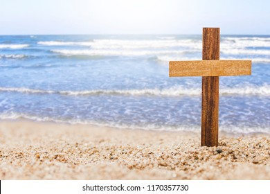 wooden cross on beach with blurred seascape background, christian concept show God's love wide and deep like the sea