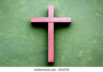 Wooden cross on green wall