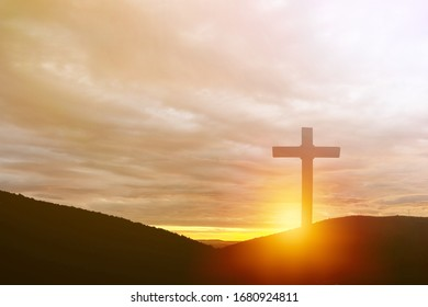 The wooden cross on mountain on the sunset background