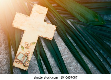 wooden cross on palm leaf on the ground.Palm sunday and easter day concept.