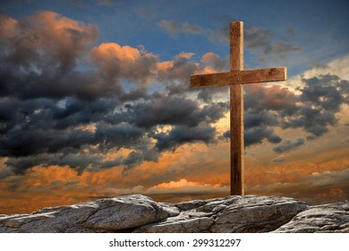 Wooden cross on rocky hill at sunset