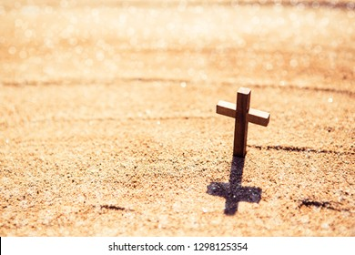 wooden cross on sand at the beach against sun light with copy space for your text, christian conceptual image
