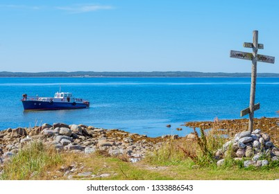 Wooden cross on the shore of the White Sea and a ship at Anzersky Island. Solovky Islands, Russia
