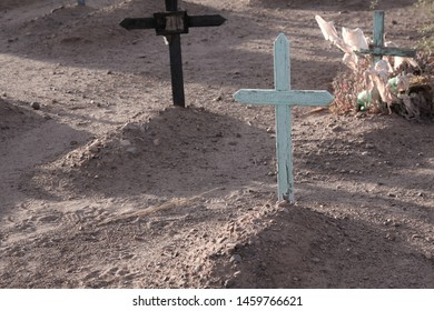 Wooden cross is on a simple grave of mounds