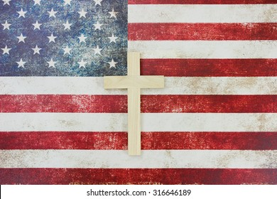 Wooden cross on vintage American flag canvas background