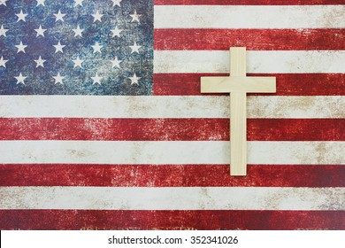 Wooden cross on vintage rustic American flag canvas background; red, white and blue Memorial Day and religious background with copy space