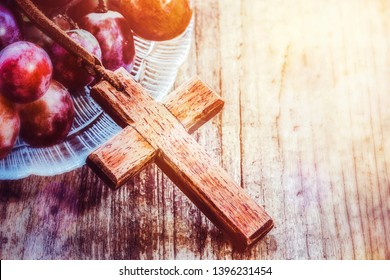 Wooden cross over grape in glass plate on old wooden background, christian symbol Jesus is the true vine from bible verses John 15:1
