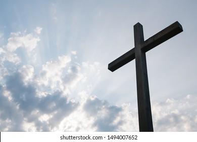 Wooden cross over sunrise background