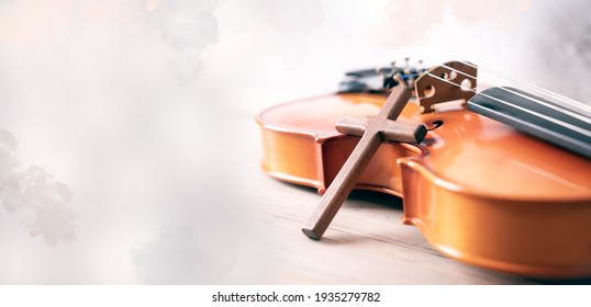 Wooden cross over violin on white old background. selective focus, Copy space.
