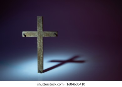 Wooden cross photograph with harsh lighting to create shadow cast onto backgroun.