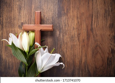 Wooden cross and white lily on rustic table