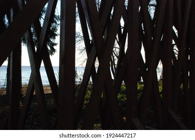 Wooden crossed socks and boards. Wooden structure made of many planks and beams. The boards crisscross each other. Behind the boards you can see the coast and the water of the bay.