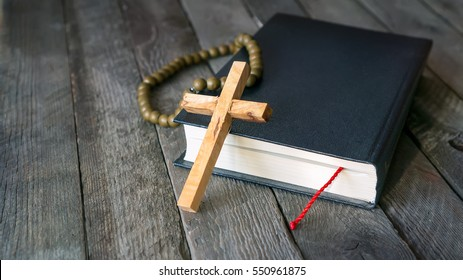 Wooden crucifix, Holy Bible and vintage rosary beads. Religion concept