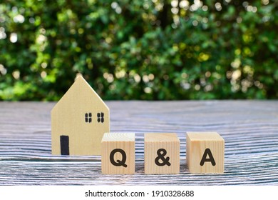 Wooden cube with Q and A on wood background.