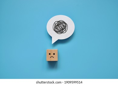 A wooden cube with a sad face with a tangle of thoughts in its head. A person can't collect his thoughts