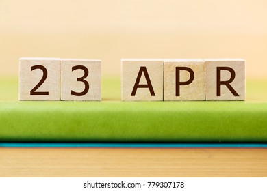 Wooden cube shape calendar for APR 23 on green book, table