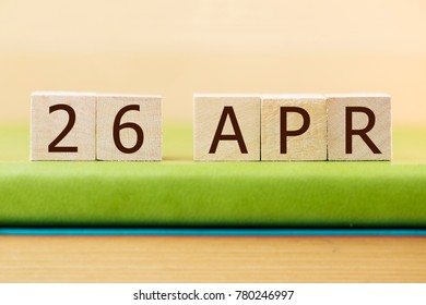 Wooden cube shape calendar for APR 26 on green book, table.