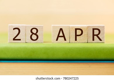 Wooden cube shape calendar for APR 28 on green book, table.