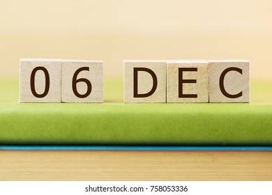 Wooden cube shape calendar for DEC 6 on green book, table.