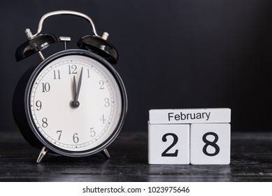 Wooden cube shape calendar for February 28 with black clock on black background. Copy space.