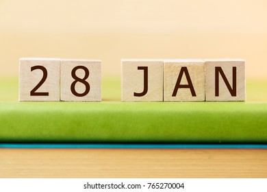 Wooden cube shape calendar for JAN 28 on green book, table.
