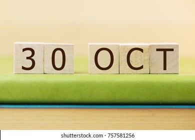 Wooden cube shape calendar for OCT 30 on green book, table.