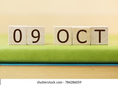 Wooden cube shape calendar for OCT 9 on green book, table.
