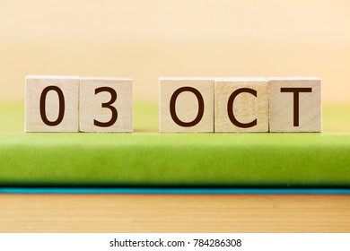 Wooden cube shape calendar for OCT 3 on green book, table.