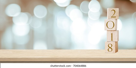Wooden cubes with 2018 on perspective wood over blur bokeh background, banner with copy space for text, new year template