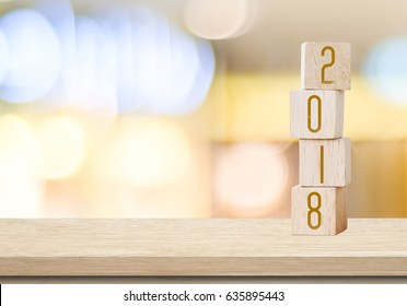 Wooden cubes with 2018 on table over blur bokeh background with copy space for text, new year and christmas card background,template