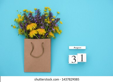 Wooden cubes calendar August 31 and field colorful rustic flowers in craft package on blue background. Greeting card Flat Lay Concept goodbye summer Template with copy space for text and design.