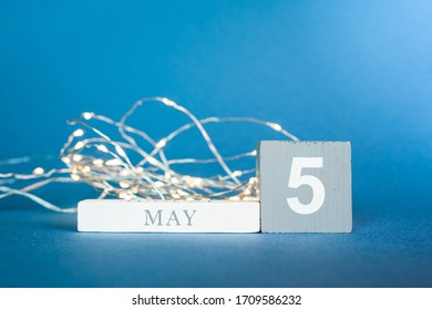 Wooden cubes of a calendar with the date may 5 and glowing garlands with warm yellow light on a blue background.