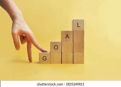 Wooden cubes in the form of a ladder on which it is written: goal. Moving towards the goal