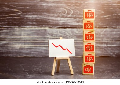 Wooden cubes with the image of the dollars and the arrow down. Financial and economic crisis. Drop in profits. Salary reduction. Bankruptcy. Low income. Capital outflow. Economic sabotage