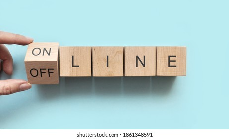 Wooden cubes with the inscription: online and offline. Choose between online and offline in everything