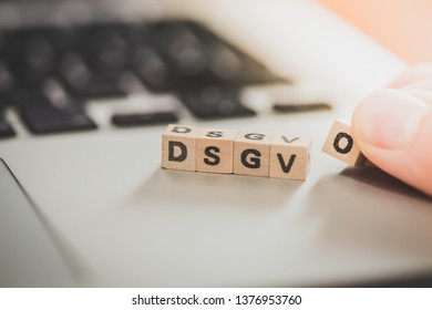 """Wooden cubes with the letters """"DGSVO"""" for Datenschutzgrundverordnung are lying on a laptop"""