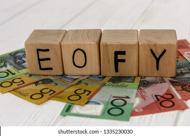 Wooden cubes with letters EOFY on australian dollar banknotes