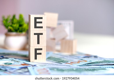 Wooden cubes with the letters ETF arranged in a vertical pyramid on banknotes, green plant in a flower pot on the background. ETF - short for Exchange-Traded Fund, business concept.