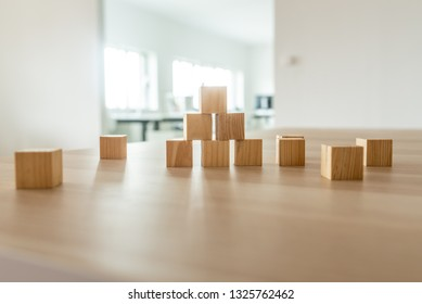 Wooden cubes positioned in a pyramid shape on office desk in a conceptual image.