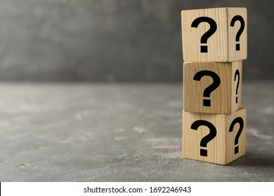 Wooden cubes with question marks on grey stone table. Space for text