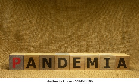 Wooden cubes with red and black word PANDEMIA on sackloth background. Pandemia and Covid-19 concept.