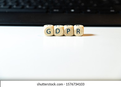 Wooden cubes with saying GDPR together with a black keyboard on white background