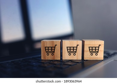 Wooden cubes with shopping cart on laptop keyboard. Online Shopping concept