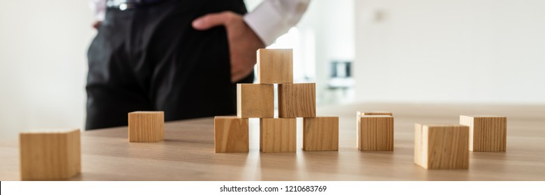 Wooden cubes stacked in pyramid on office desk with businessman standing in background.