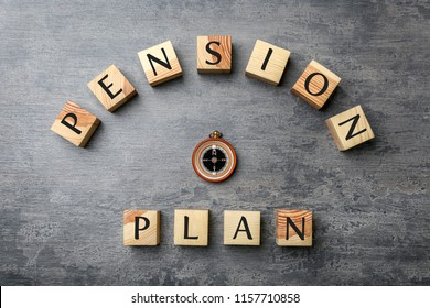 Wooden cubes with text PENSION PLAN and compass on grey background