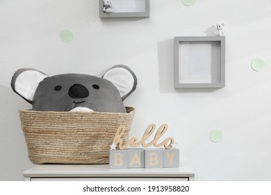 Wooden cubes and wicker basket on chest of drawers indoors. Children's room interior
