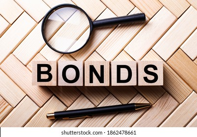 Wooden cubes with the word BONDS stand on a wooden background between a magnifying glass and a handle
